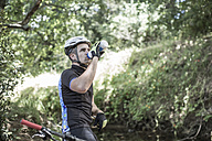 Man on mountainbike in forest drinking water - ZEF007909