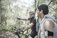Man on mountainbike in forest talking to young man - ZEF007912