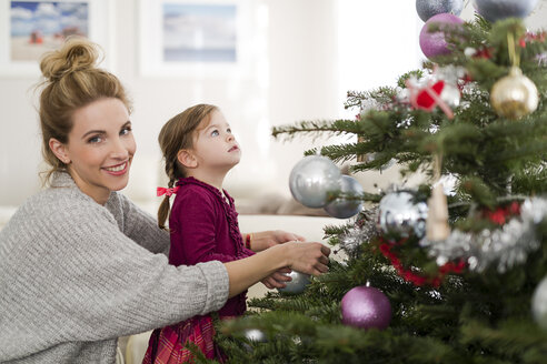 Portrait of smiling woman decorating Christmas tree with her little daughter in the living room - SHKF000435