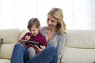 Mother and her little daughter sitting on couch in the living room looking at digital tablet - SHKF000438