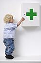 Blond little girl opening medicine cabinet - GUFF000220