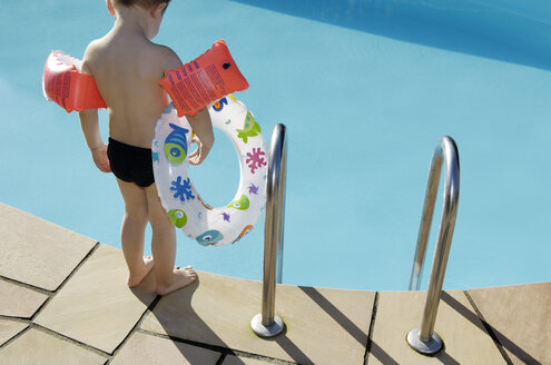 Back view of little boy with floating tire and water wings standing at pool edge - GUFF000229