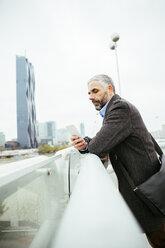 Austria, Vienna, businessman standing on Reichsbruecke looking at his smartphone - AIF000216