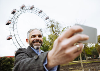 Austria, Vienna, portrait of smiling businessman taking a selfie at Prater - AIF000224