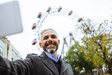 Austria, Vienna, portrait of smiling businessman taking a selfie at Prater - AIF000227