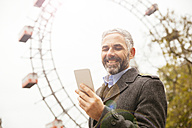 Austria, Vienna, portrait of smiling businessman looking at his smartphone at Prater - AIF000230