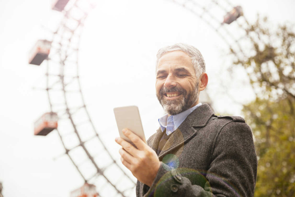 Austria, Vienna, portrait of smiling businessman looking at his smartphone at Prater - AIF000230 - AustrianImages/Westend61