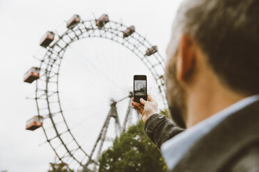 Austria, Vienna, businessman taking a picture of big wheel with his smartphone at Prater - AIF000233