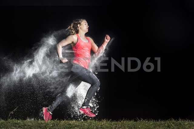 Young woman jogging in a dust cloud in front of black background - STSF000993 - Stefan Schurr/Westend61