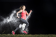 Young woman jogging in a dust cloud in front of black background - STSF000993