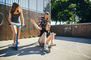 Three playful teenage friends with scooter and skateboard - AIF000259