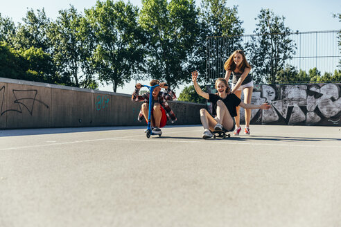 Three playful teenage friends with scooter and skateboard - AIF000262