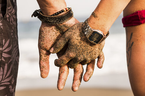 Close-up of couple holding sandy hands - SIPF000017