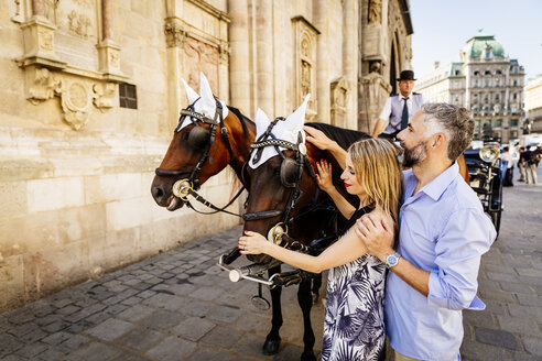 Austria, Vienna, couple stroking horse in front of St. Stephen's Cathedral - AIF000283