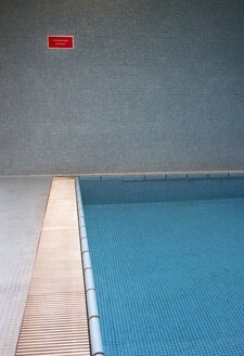 Empty indoor swimming pool with sign at the wall - WWF003912
