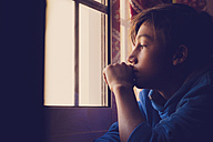 Pensive boy looking through window - SIPF000034