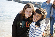 Spain, Barcelona, portrait of happy brother and sister on the beach with their parents in the background - VABF000046