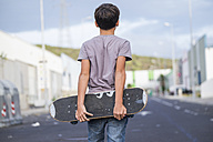 Spain, Tenerife, back view of boy holding his skateboard behind his back - SIPF000041
