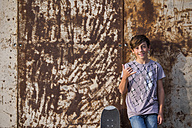 Portrait of boy leaning against rusty metal wall with his skateboard - SIPF000044
