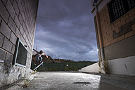 Spain, Tenerife, boy skating between two buildings - SIPF000050