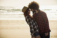 Spain, Cadiz, young couple in love standing face to face on the beach - KIJF000110