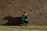 Young man crouching in front of a brick wall with digital tablet - FMKF002254