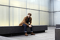 Germany, Cologne, stylish young man waiting on a stone bench - FMKF002257