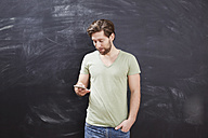 Young man sitting looking at his smartphone in front of chalkboard - FMKF002260