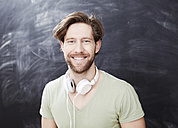 Portrait of smiling young man with headphones in front of chalkboard - FMKF002263