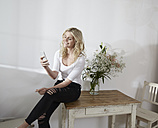 Young woman sitting on an old wooden table looking at her smartphone - FMKF002269