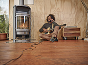 Young man with electric guitar at the fireplace talking on cell phone - RHF001220