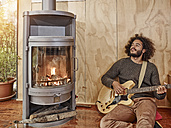 Young man playing electric guitar at the fireplace - RHF001226