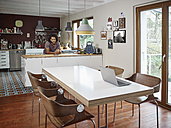 Young man in open plan kitchen - RHF001229