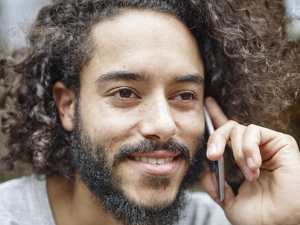 Smiling young man on cell phone - RHF001250