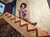 Young man on wooden stairs looking at cell phone - RHF001271
