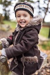 Portrait of happy little girl on a playground in autumn - MGOF001239