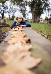 Portrait of little girl playing with autumn leaves in the park - MGOF001248