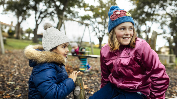 Two girls watching something on a playground in autumn - MGOF001251