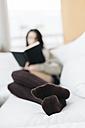 Feet of woman relaxing on balcony - JRFF000291