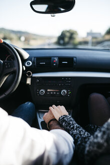 Rear view of the hands of a couple on the gearbox while driving the car - JRFF000314