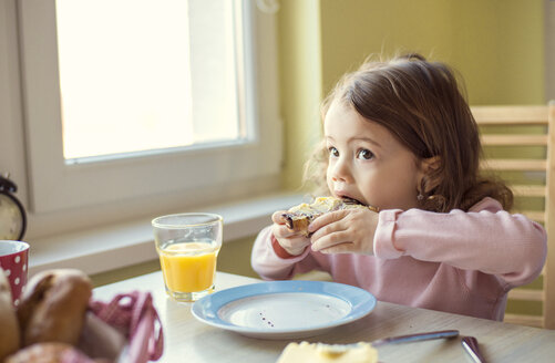 Portrait of little girl eating a croissant at breakfast table - HAPF000114