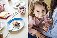 Portrait of smiling little girl cuddling with her mother at breakfast table - HAPF000129