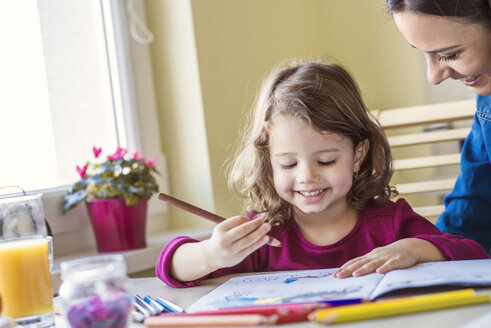 Portrait of smiling little girl painting with coloured pencils - HAPF000132