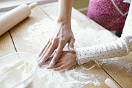 Woman's and her little daughter's hands on table top covered with flour, close-up - HAPF000138