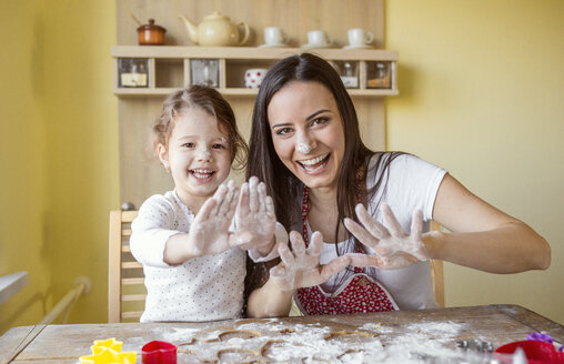 Portrait of laughing mother and her little daughter baking together - HAPF000156