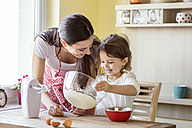 Portrait of smiling little girl and her mother baking together - HAPF000162