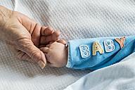Senior woman's hand holding baby's hand - DEGF000605