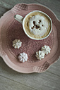 Cup of white coffee with chocolate shaving and meringues on a plate - ASCF000457
