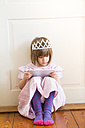 Little girl dressed up as a princess looking at digital tablet - LVF004415