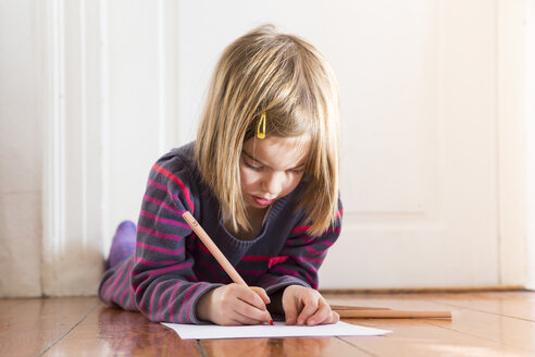 Little girl lying on the floor drawing something - LVF004420